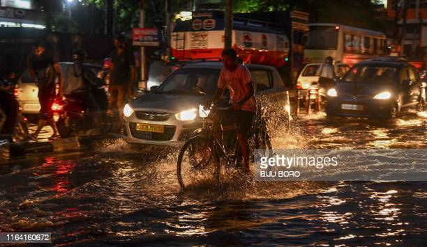 Commuters ride their bike and cars along a flooded street after heavy monsoon rains in Guwahati, the capital city of India's northeastern state of...