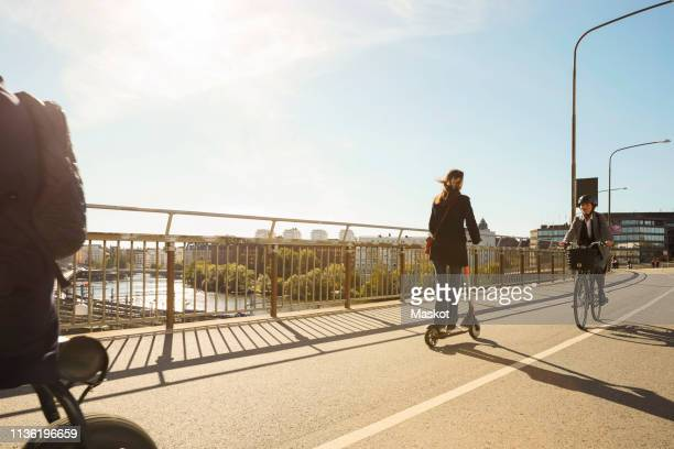 commuters riding electric vehicles on bridge against blue sky - electric scooter stock pictures, royalty-free photos & images