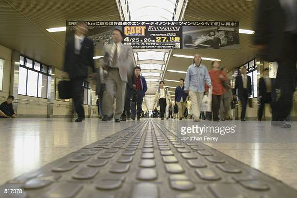 Commuters rush past a billboard in Utsonomiya railway station for the upcoming Bridgestone Potenza 500 round three of the CART Fed Ex Championship...