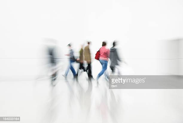 Commuters Rushing in White Interior, Blurred Motion