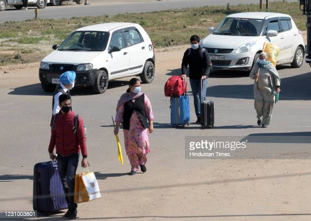 Commuters seen carrying their luggage on foot at Mullanpur barrier during the pan-India Chakka Jaam called by farmers against the new farm laws, on...