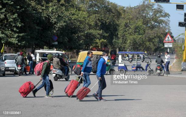 Commuters seen carrying their luggage on foot near the Airport during the pan-India Chakka Jaam called by farmers against the new farm laws, on...