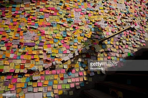 Commuter's shadow is cast on notes hanging on a wall outside the Central Government Offices in Hong Kong, China, on Thursday, Oct. 9, 2014. Hong Kong...