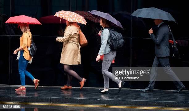 Commuters shelter from the rain beneath umbrellas as they walk near London Bridge in London on September 29 2017 / AFP PHOTO / NIKLAS HALLE'N