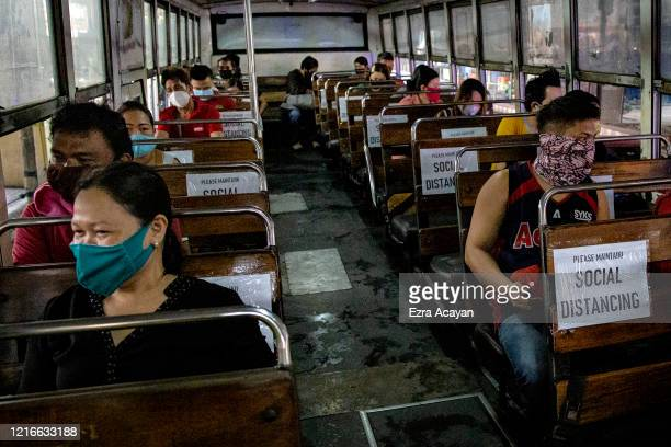 Commuters sit inside a bus with seats spaced to observe social distancing on the first day of relaxed quarantine measures on June 1, 2020 in...