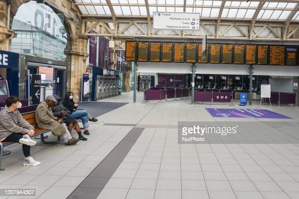 Commuters sit on a bench as they wait on an empty train station in Sheffield , England , 22 March 2020.
