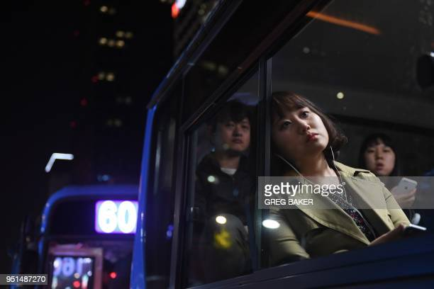 Commuters sit on a bus the night before the interKorean summit in Seoul on April 26 2018 North Korea's leader Kim Jong Un and the South's president...