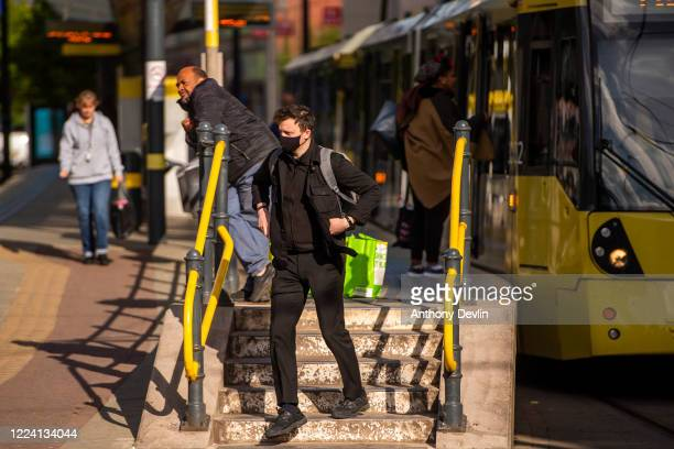 Commuters, some in face masks, board and exit a MetroLink tram in Manchester City centre on May 11, 2020 in Manchester, United Kingdom. The prime...