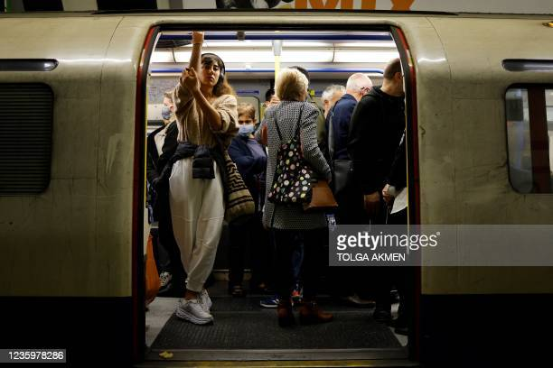Commuters, some wearing face coverings to help prevent the spread of coronavirus, wait for a Transport for London underground train to leave from a...