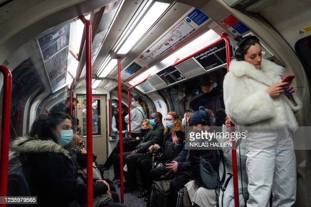 Commuters, some wearing face coverings to help prevent the spread of coronavirus, travel in a Transport for London underground train carriage in...