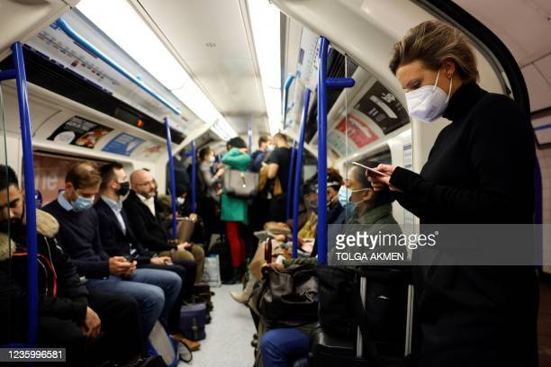 Commuters, some wearing face coverings to help prevent the spread of coronavirus, ride a Transport for London underground train in London on October...