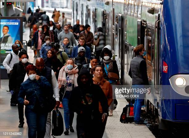 Commuters, some wearing face masks, leave a train arriving at the Gare du Nord train station in Paris on April 29 on the 44th day of a lockdown in...