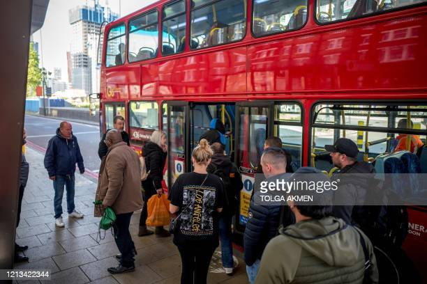 Commuters, some wearing PPE , including a face mask as a precautionary measure against COVID-19, wait to board a TFL red London bus at Vauxhall bus...