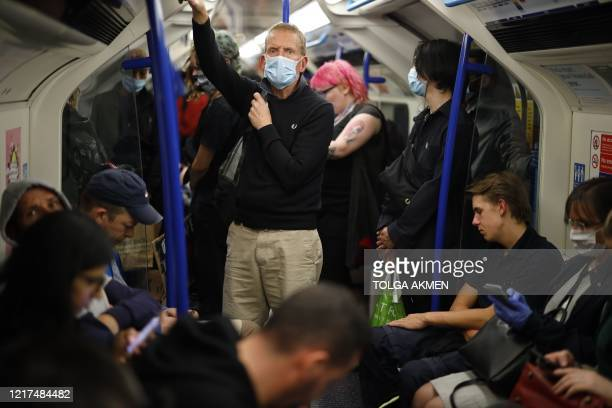 Commuters, some wearing PPE , including a face mask as a precautionary measure against COVID-19, stand on a busy Transport for London Victoria Line...
