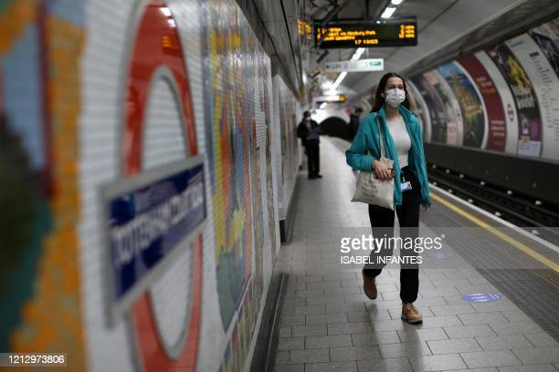 Commuters, some wearing PPE including face masks as a precautionary measure against COVID-19, travel by public transport during the evening 'rush...