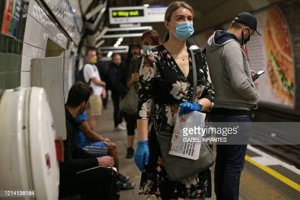 Commuters, some wearing PPE , including face masks as a precautionary measure against COVID-19, travel on a TfL Victoria line underground trains...