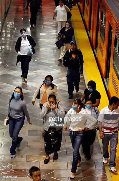 Commuters some wearing surgical masks to help prevent contamination with swine flu exit from a train on May 1 2009 in Mexico City Mexico Traffic...