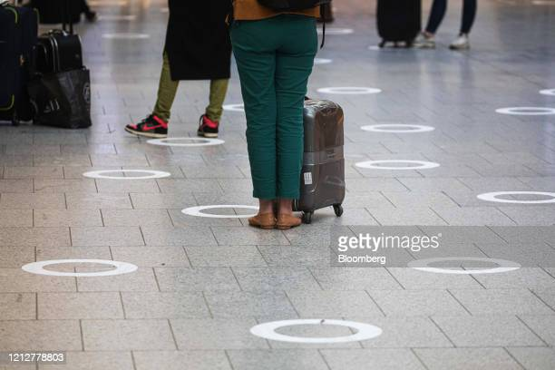 Commuters stand around social distancing markers at Gare Montparnasse railway station in Paris France on Tuesday May 12 2020 The Paris metro...