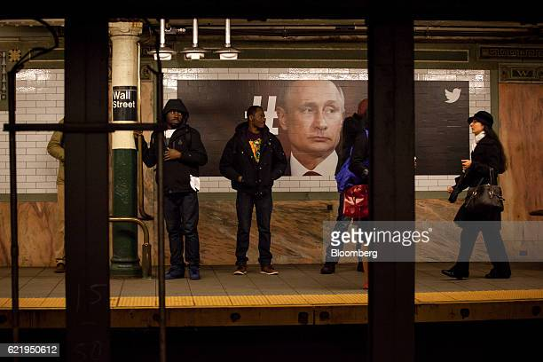 Commuters stand in front of a poster displaying an image of Vladimir Putin Russia's president at the Wall Street subway station in New York US on Wed...
