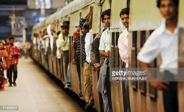 Commuters stand in the doorways of a crowded local train as it leaves Churchgate railway station in Mumbai 13 July 2006 The death toll from a wave of...