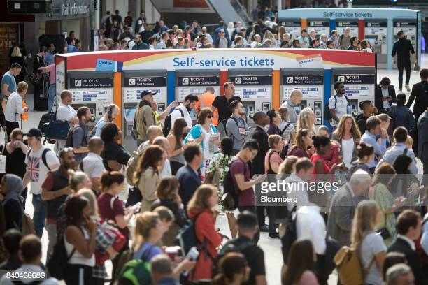 Commuters stand near selfservice ticket machines as they look at display boards for train information after overrunning renovation works delayed...