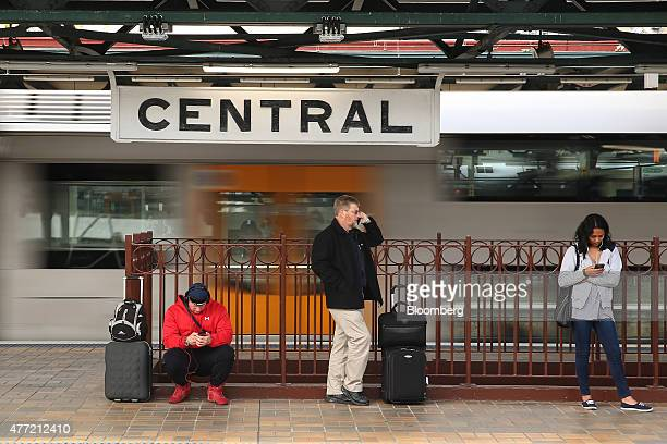 Commuters stand on a platform as a train travels past at Central Station in Sydney Australia on Tuesday June 9 2015 Australian wages fell in the...