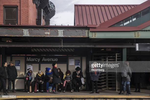 Commuters stand on a platform at the Marcy Avenue subway station in the Brooklyn borough of New York US on Wednesday Dec 20 2017 New York's...