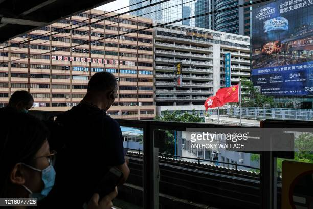 Commuters stand on a train platform in front of a view of the Chinese and Hong Kong flags hoisted above a fire station in Hong Kong on May 29 2020...