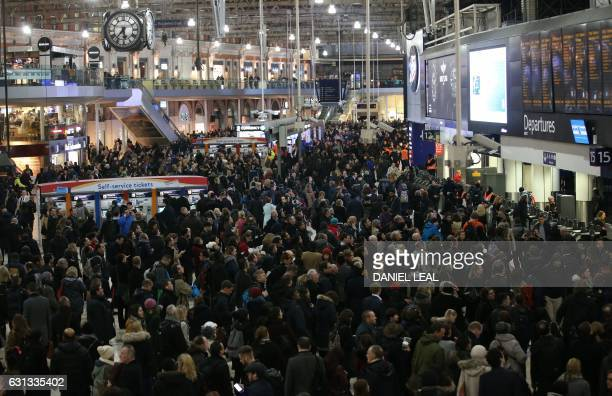 Commuters stand on the concourse at Waterloo station in central London on January 9 minutes before a 24hour tube strike is due to end Millions of...