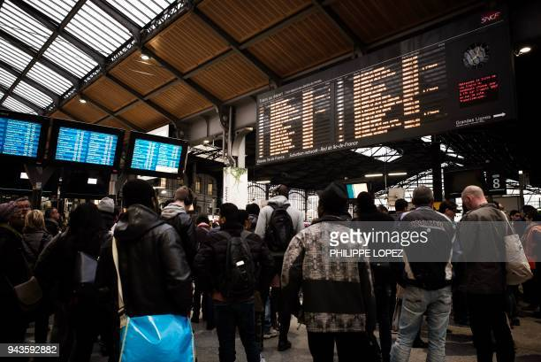 Commuters stand under information boards at the gare SaintLazare in Paris on April 9 2018 as French rail workers launched their latest twoday strike...