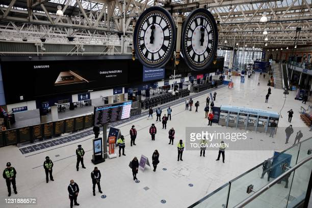 Commuters take part in a minute's silence on the first anniversary of the first national Covid-19 lockdown, at Waterloo Station in central London on...