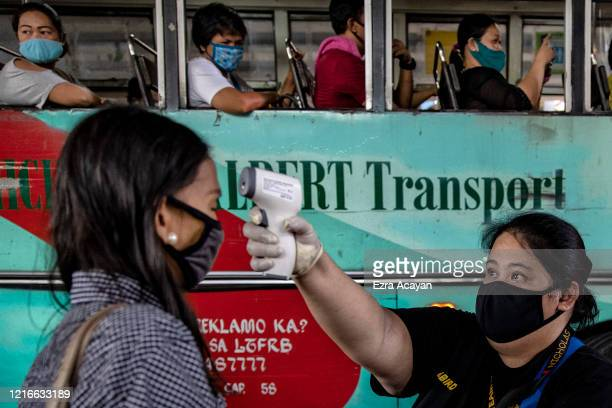 Commuter's temperature is checked by a worker before being allowed to board a bus on the first day of relaxed quarantine measures on June 1, 2020 in...