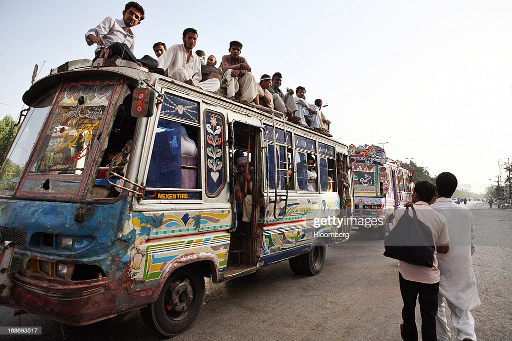 Commuters travel inside and on the rooftop of a bus in Karachi, Pakistan, on Monday, May 13, 2013. Nawaz Sharif was headed for a record third term as prime minister of Pakistan as unofficial results from a landmark election gave him the convincing win he sought to tackle a slumping economy and growing militancy. Photographer: Asim Hafeez/Bloomberg via Getty Images