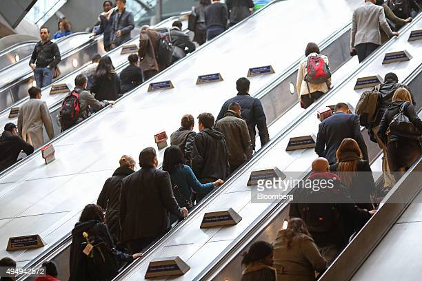 Commuters travel on escalators at a London Underground station in the Canary Wharf business financial and shopping district in London UK on Friday...