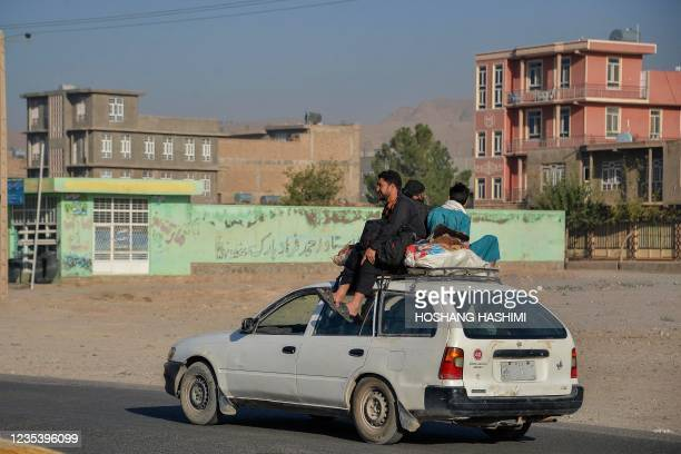 Commuters travel sitting atop a car in Herat on September 21, 2021.