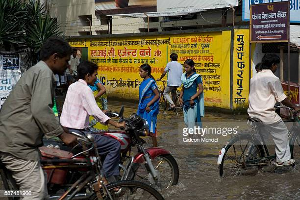 Commuters travel through a waterlogged street in the centre of the town of MuzaffarpurThis is in the province of Bihar which was devastated by the...