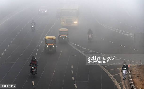 Commuters travel with their headlights switched on during a cold foggy morning in New Delhi on December 8 2016 / AFP / Money SHARMA