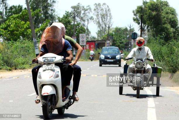 Commuters travelling with their faces covered on a hot summer day on May 25, 2020 in Patiala, India.