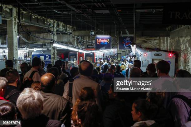 Commuters try to get a train as they wait for service to be restored after a severe thunderstorm downed trees that caused power outages resulting in...