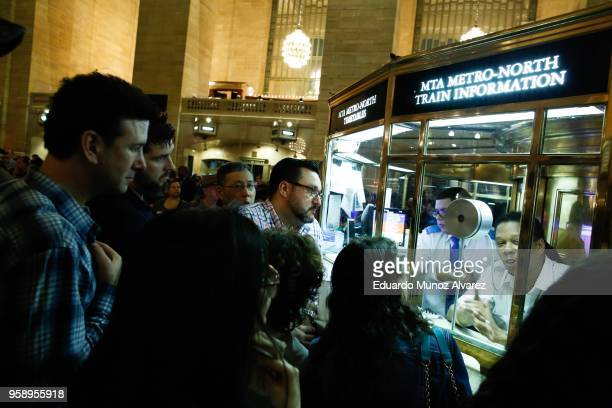 Commuters try to get information about alternative routes as they wait for train service to be restored after a severe thunderstorm downed trees that...