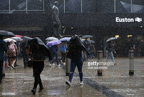 Commuters use coats and umbrellas to shelter from a heavy downpour of rain as they pass Euston Station in central London on June 23 2016 Millions of...