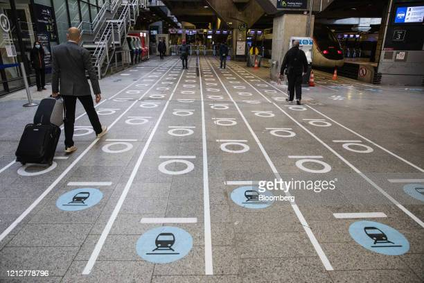 Commuters use social distancing marker lanes at Gare Montparnasse railway station in Paris France on Tuesday May 12 2020 The Paris metro authority is...