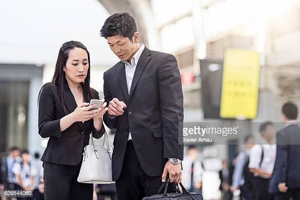 Commuters using mobile phone at station