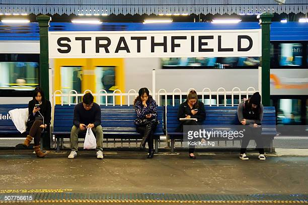 Commuters using their mobile phones while waiting for a train at Strathfield Railway Station.
