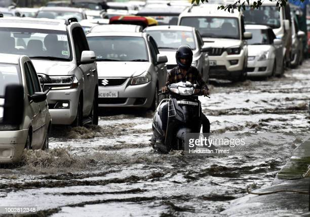 Commuters wade trough the water logged road after heavy rain at Bhairon Marg near Old Fort on July 20 2018 in New Delhi India Daily commuters had a...