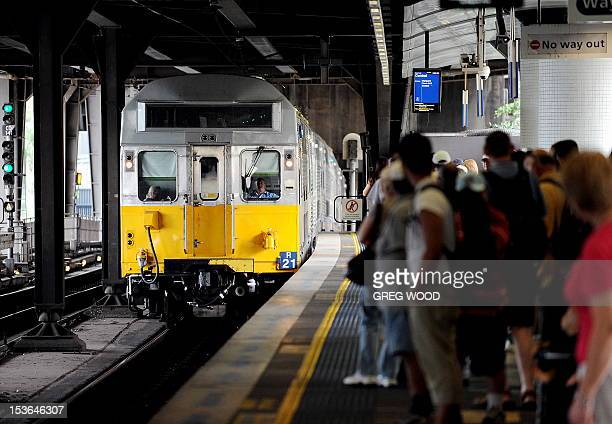 Commuters wait as a New South Wales Government CityRail commuter train arrives at the Circular Quay railway station in Sydney on February 2 2010 AFP...