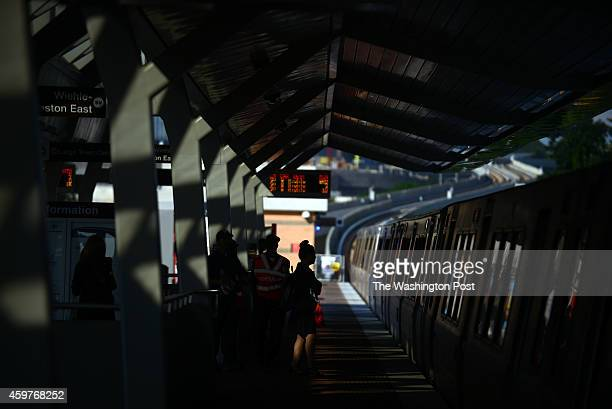 Commuters wait at Tysons Corner Metro station to board a Silver Line Metro train westbound to Reston during morning commute in Tysons Corner VA...
