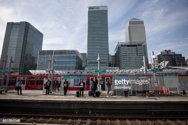 Commuters wait for a Docklands Light Railway near the offices of HSBC Holdings Plc center and the Canary Wharf financial business and shopping...