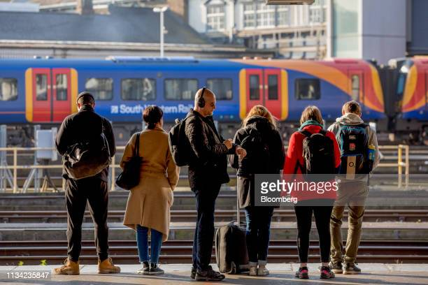 Commuters wait for a passenger train on a platform at Clapham Junction railway station in London UK on Monday April 1 2019 Since the June 2016...