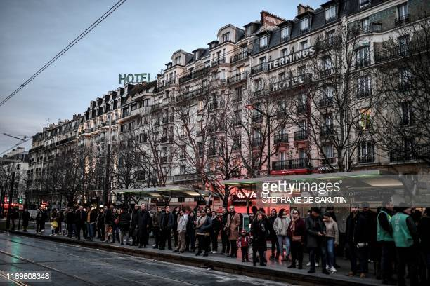 TOPSHOT Commuters wait for a tramway in Paris on December 19 on the 15th day of a nationwide multisector strike against the government's pensions...